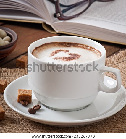 Cup of latte on the old wooden background