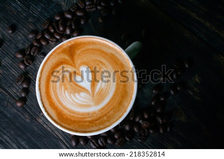 Cup of latte or cappuccino and coffee beans on wooden desk  - stock photo