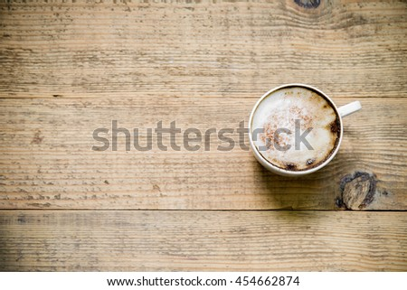 Cup of latte or cappuccino coffee on wooden table. Top view with copy space