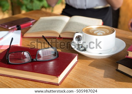 cup of latte or cappuccino coffee with a book in coffee shop