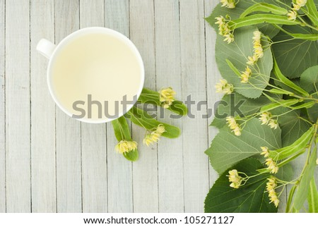 cup of lime tea and linden flowers, bright wooden table, high angle view