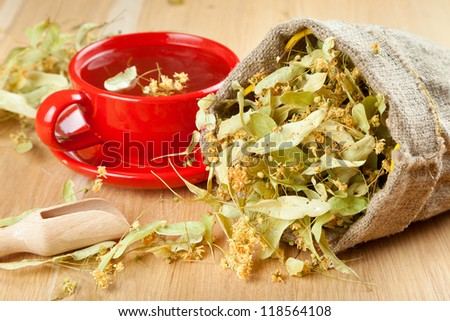 cup of linden tea and flowers in canvas bag on wooden table - stock photo