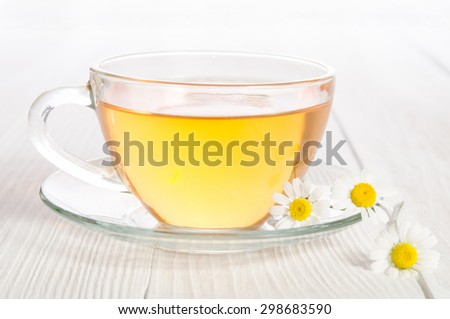 Cup of medicinal chamomile tea  on the wooden table - stock photo