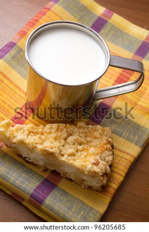 cup of milk and a piece of cake on the table - stock photo