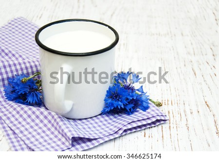 Cup of milk,  and cornflowers on a old wooden background - stock photo