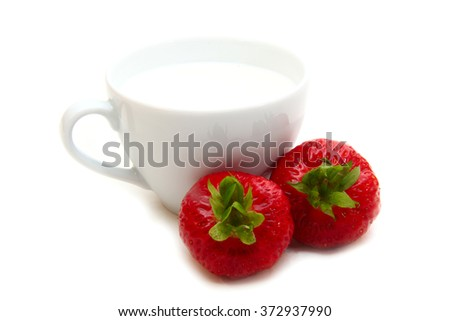 cup of milk and strawberries on a white background