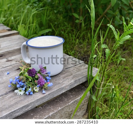 Cup of milk with bunch of wildflowers on old wooden table over grass background, summer rural still life  - stock photo