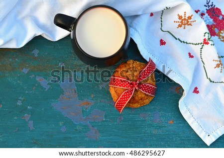 Cup of milk with homemade oat cookies on the blue wooden table, top view