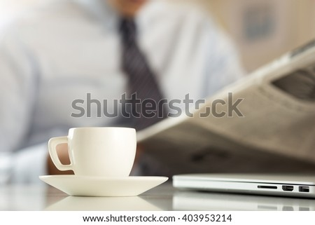 Cup of morning coffee on worktable with business analyst hold in hands and read newspaper on background. Price quotation on the exchange, relaxing at workplace, or football match result concept - stock photo