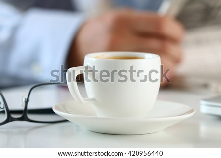 Cup of morning coffee on worktable with business analyst hold in hands and read newspaper on background.