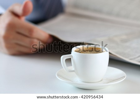 Cup of morning coffee on worktable with businessman and read newspaper on background.  - stock photo