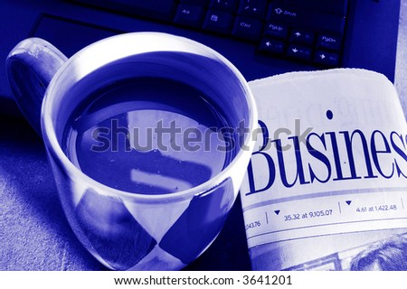 Cup of morning coffee with laptop and newspaper - stock photo