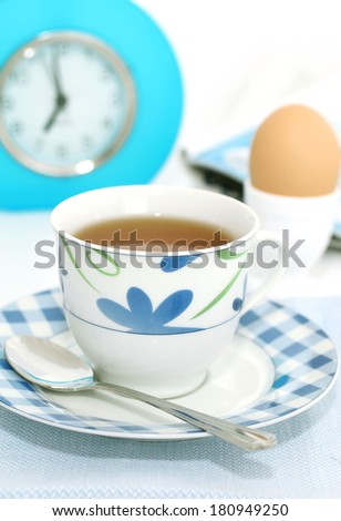 cup of morning tea and alarm clock  - stock photo