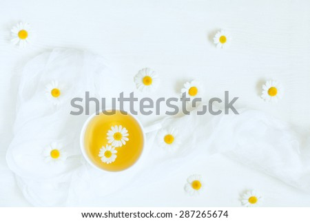 Cup of natural chamomile herbal tea with blooming camomile flowers on white table background. Natural light rustic style. Natural aromatherapy relaxation beverage. - stock photo