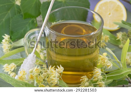 Cup of natural linden tea with sugar stick, lemon and lime flowers