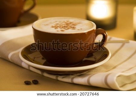 cup of plain white coffee on towel, candle in background - stock photo