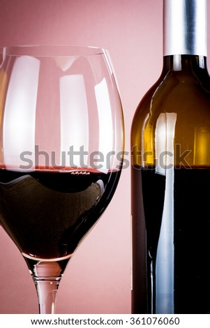 Cup of red wine and bottle of wine
