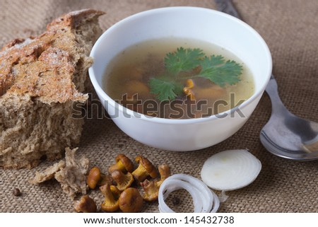 Cup of soup with chanterelle mushrooms, onion and bread