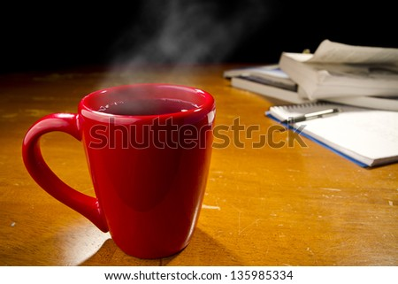 Cup of steaming coffee with text books and notepad in background - stock photo