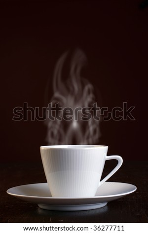 Cup of steaming hot coffee over dark background. - stock photo