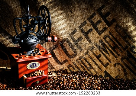 Cup of steaming hot coffee with coffee beans, coffee grinder, and coffee beans bag in background.