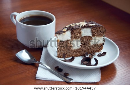 Cup of strong espresso coffee with a slice of tasty chocolate cake on a saucer with a chess decoration, covered with almond chips on top and decorated with chocolate slices on a plate. On wooden table