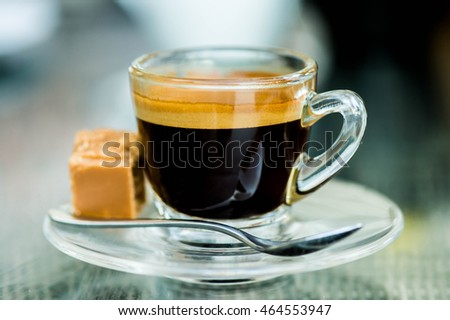 Cup of Strong Single Shot Espresso Coffee in a Glass Cup With Fudge On A Table