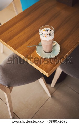Cup of sweet cacao with chocolate and whipped cream on rustic wooden table in cafe. Top view. - stock photo