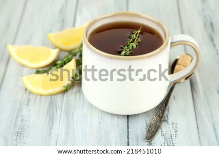 Cup of tasty herbal tea with thyme and lemon on wooden table - stock photo