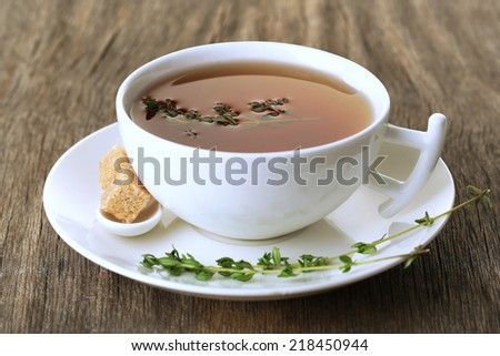 Cup of tasty herbal tea with thyme on wooden table - stock photo
