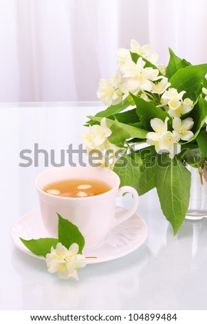 Cup of tasty jasmine tea and flowers