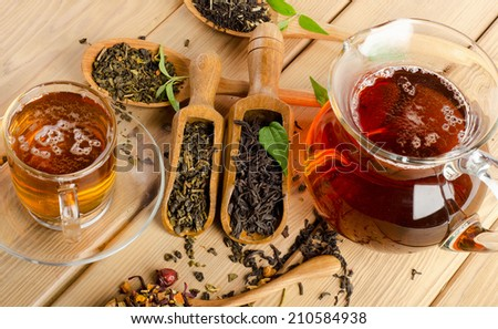 Cup of tea and assortment of dry tea in spoon on a  wooden background. Selective focus - stock photo