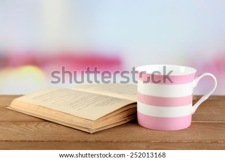 Cup of tea and book on table, on bright background - stock photo