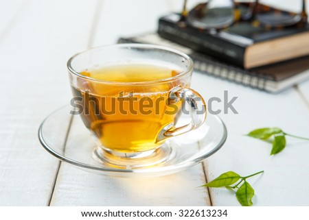 Cup of tea and book on white wooden table - stock photo
