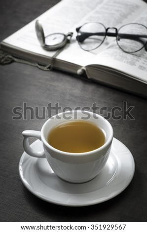 Cup of tea and book on wooden table, close up