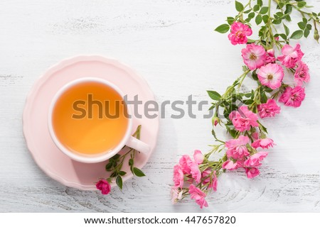 Cup of tea and branch of small pink  roses on rustic table. - stock photo