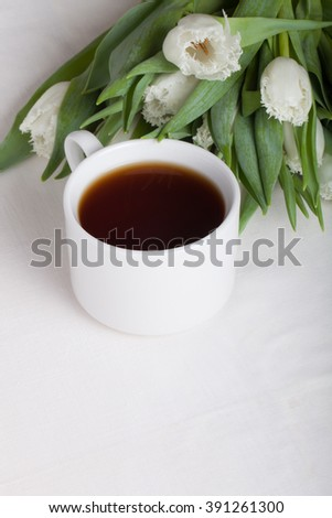 Cup of tea and bunch of spring tulips on the table. Shallow depth of field. Selective focus. - stock photo