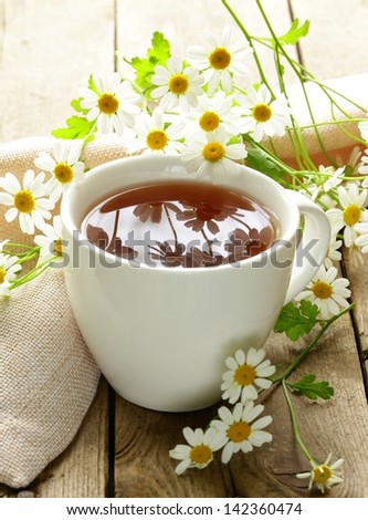 cup of tea and chamomile flowers on a wooden table - stock photo