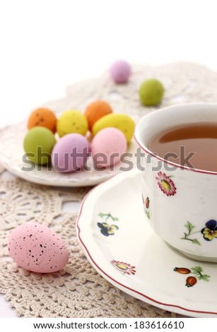 cup of tea and colorful easter eggs on beautiful napkin - stock photo