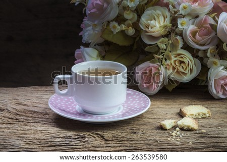Cup of tea and cookie on wooden table with flowers, still life - stock photo