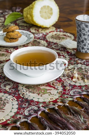 cup of tea and cookies over chinese tablecloth