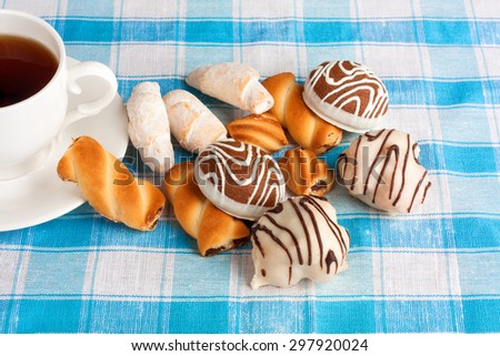 Cup of tea and delicious cookies on blue checkered tablecloth  - stock photo