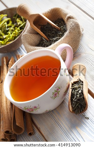 Cup of tea and dried tea leaves on wooden planks