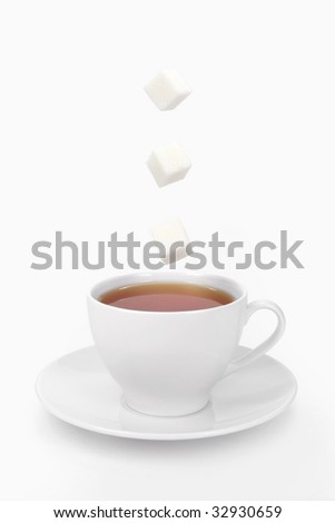 Cup of tea and falling sugar cubes - stock photo