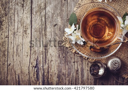 Cup of tea and jasmine flower on rustic wooden table, Top view. - stock photo