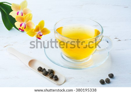 Cup of tea and leaves of green tea braided in balls on white wooden background. Green tea.  Cup of green tea.  - stock photo