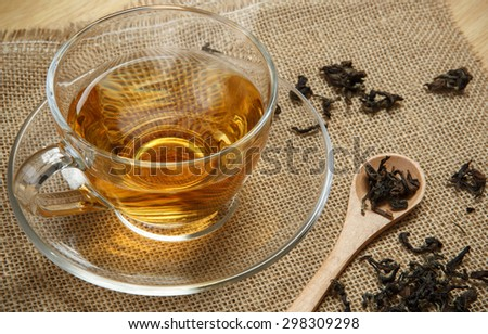 Cup of tea and leaves tea on brown jute background - stock photo