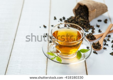 Cup of tea and leaves tea on white wooden table