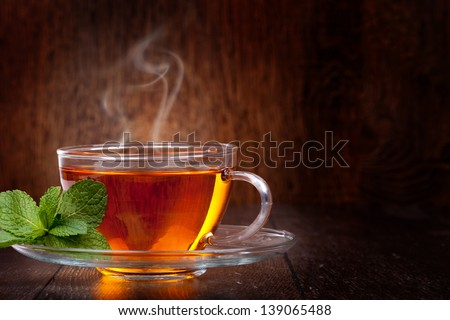 Cup of tea and mint on a wooden background - stock photo