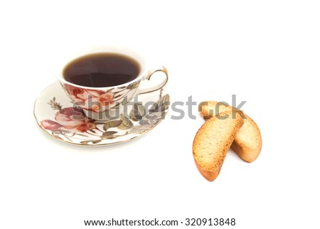 cup of tea and pair of crackers on white - stock photo